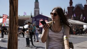 A woman using a smartphone speaks on Red Square in Moscow, in front of the Kremlin.  stock video footage