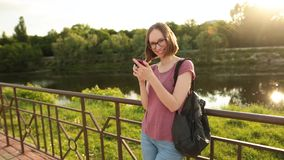 Woman using smartphone standing outdoors on the bridge. Hipster girl browsing Internet on a phone, texting and. Smiling woman in glasses with a leather backpack stock video footage