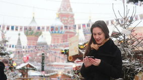 Woman using a smartphone standing in the winter on the Red Square in Moscow, in front of St. Basil Cathedral. Young beautiful woman talking on the phone using a stock video