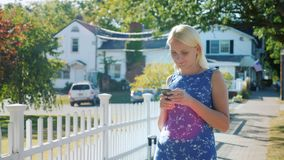 A woman is using a smartphone. It stands on the street near a white fence, behind the American flag. A typical American. Town. 4K video stock footage