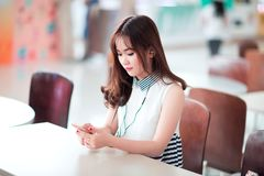 Woman using smartphone at table Stock Images