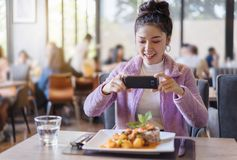 Woman using smartphone take photo of food before eating in restaurant. Woman using smartphone take photo of food before eating in the restaurant royalty free stock photos