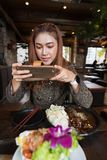 Woman using smartphone taking a photo of food in restaurant stock images