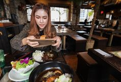 Woman using smartphone taking a photo of food in restaurant royalty free stock image