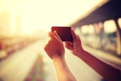 Woman using smartphone taking photo in modern city Stock Photo