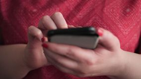 Woman using a smartphone texting message. Handheld slow motion, 60fps 4K shot. Woman using a smartphone texting message. Close up shot of female hands. Handheld stock footage