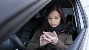 Woman using smartphone, texting message while sitting in car. 4k , high quality stock video