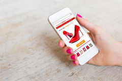 Woman using smartphone to buy shoes online. Woman using smart phone to buy shoes online royalty free stock images