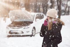 Woman using smartphone to call road assistance. Winter and vehicle concept. royalty free stock photography