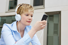 Woman using smartphone to listen to music Royalty Free Stock Image
