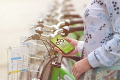 Renting bicycle from urban bicycle sharing station Stock Photos