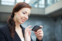 Woman using smartphone on the way. Attractive young woman using her smartphone on the way in the city Stock Photos