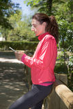 Woman using smartphone in wooden footbridge Royalty Free Stock Photography
