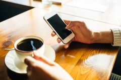 Woman using smartphone on wooden table in cafe royalty free stock photography