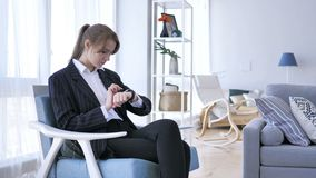 Woman Using Smartwatch while Sitting on Sofa. 4k , high quality stock footage