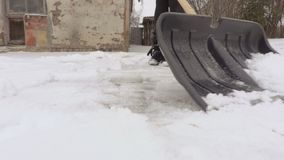Woman using snow shovel close up. In winter day stock video