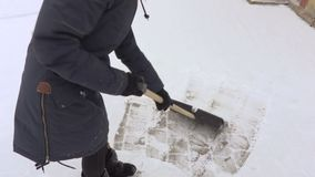 Woman using snow shovel in snow covered yard. In winter day stock video footage