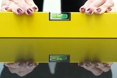 A woman using a spirit level for home work Royalty Free Stock Images