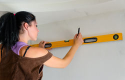 Woman using a spirit level while renovating Stock Images