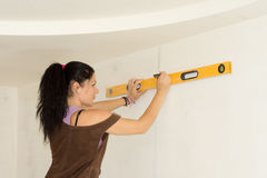 Woman using spirit level to work out measurements royalty free stock photography