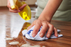 Woman Using Spray Cleaner On Wooden Surface Royalty Free Stock Image