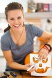 Woman using stencils to carve pumpkin Jack-O-Lantern Royalty Free Stock Photos