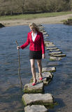 Woman using stepping stones to cross a river. Woman holding a stick for support crossing a river using stepping stones. Team building businesswoman in the Welsh Royalty Free Stock Photos