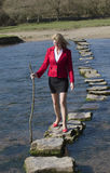 Woman using stepping stones to cross a river. Woman holding a stick for support crossing a river using stepping stones. Team building businesswoman in the Welsh Stock Images