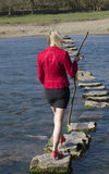 Woman using stepping stones to cross a river Royalty Free Stock Image