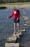 Woman using stepping stones to cross a river. Woman holding a stick to test depth of water crossing a river using stepping stones. Businesswoman on a team Royalty Free Stock Images