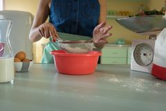 Woman using strainer in kitchen Royalty Free Stock Photos