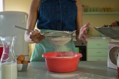 Woman using strainer in kitchen Royalty Free Stock Photography