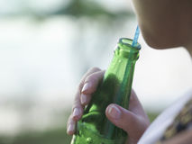 Woman Using Straw To Drink From Bottle Royalty Free Stock Images
