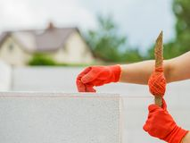 Woman using string as level in wall construction stock image