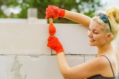 Woman using string as level in wall construction royalty free stock photo