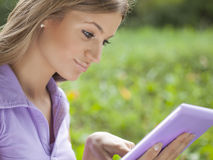Woman using stylish tablet computer in park Royalty Free Stock Image