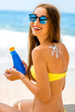 Woman using sun cream on the beach royalty free stock image