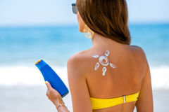 Woman using sun cream on the beach Stock Images