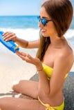 Woman using sun cream on the beach Stock Photography