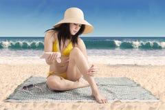 Woman using sunscreen on leg skin Stock Image