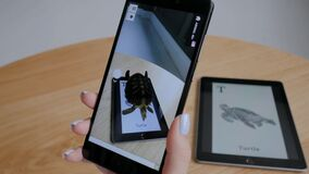 Woman using tablet with augmented reality app - virtual 3d models of animals