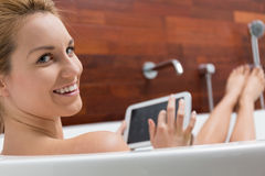 Woman using tablet in a bathtub Royalty Free Stock Image