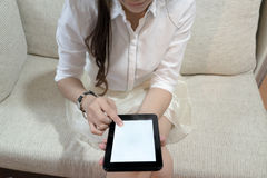Woman using tablet with blank white screen. Hands of Asian woman using her tablet with blank white screen Stock Photo