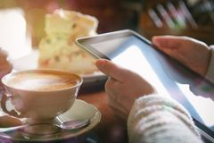 Woman using tablet in the cafe. Authentic image of woman using tablet taken in the cafe with cappuccino and meringue cake in the background Stock Photography