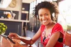 Woman using a tablet at a coffee shop, portrait Stock Photography