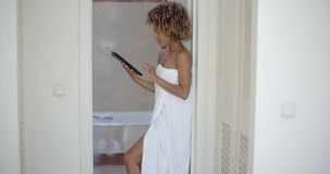 Woman Using Tablet Computer In Bathroom Stock Photo