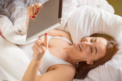 Woman using tablet computer in bed Stock Photos