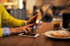 Woman using tablet computer in cafe. While drinking coffee and eating cake Stock Image