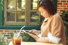 Woman using tablet computer and drinking coffee Royalty Free Stock Photos