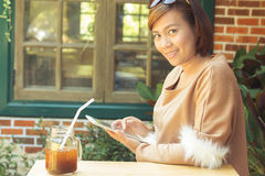 Woman using tablet computer and drinking coffee Royalty Free Stock Image